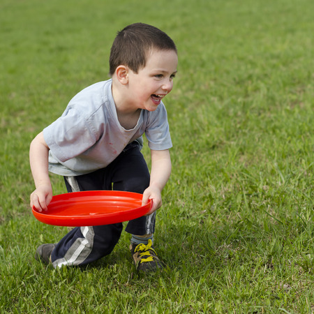 Child boy playing on a grass with a red frisbee disk. Stock Photo