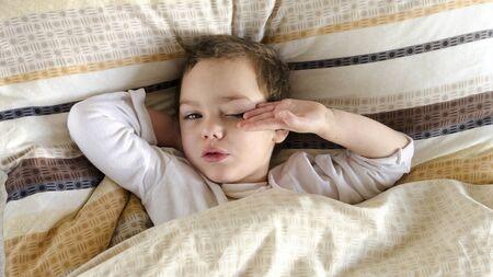 despertarse: Sleepy niño enfermo o enferma que yacen en una cama, despertarse por la mañana.