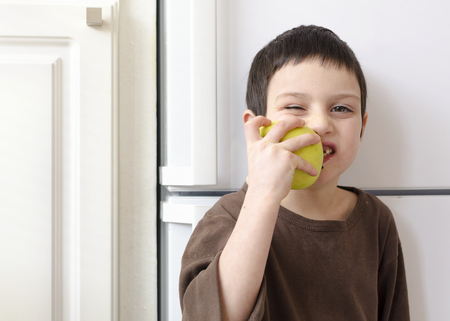 Child boy eating a green apple at home in the kitchen.