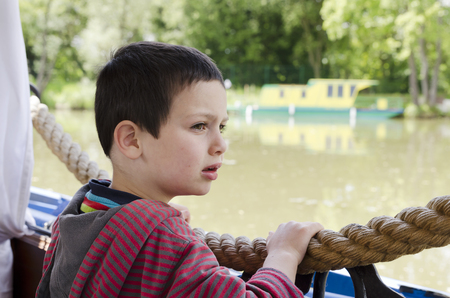 Portrait of a child boy on a river boat or barge looking at distance.