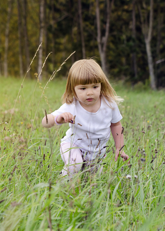 Child girl walking through a long grass at a wild meadow.