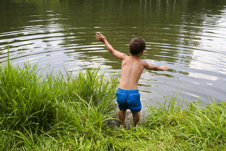 Child boy jumping into water of a lake or pond from grass bank.