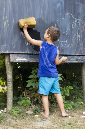 Child boy wiping blackboard in outdoor forest school clasroom, education concept. Stock Photo