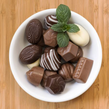Assorted chocolate pralines with mint on a plate or bowl, top view.