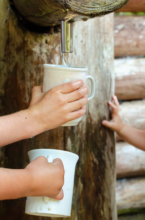 Detail of children hands hodling cups and fiilling them with drinking water from a spring Stock Photo
