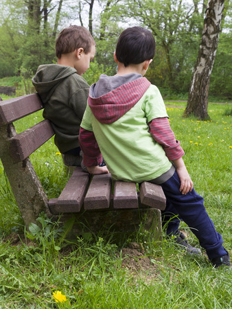 Two children friends or brothers on a bench in spring park, back view. Stock Photo