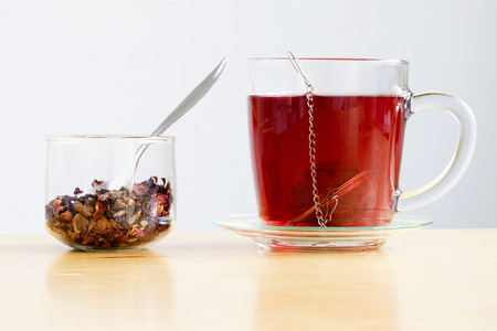 Cup or mug of loose fruit herb tea with metal ball strainer