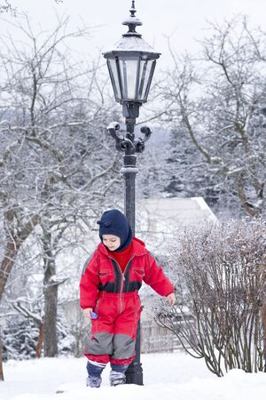 Child boy in red winter clothes in winter snow park. Stock Photo