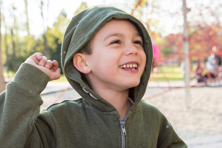 Portrait of a happy smiling child boy in a playground