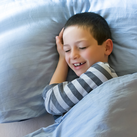bed sheet: Happy child in bed waking in the morning.