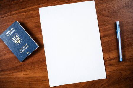 a sheet of A4 paper on the table and a Ukrainian passport with a pen, a sheet of A4 paper and a passport with a mobile phone, a blank A4 sheet and a passport with a pen near it, not filled sheet A4 Stockfoto