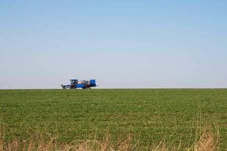 blue tractor sprinkles wheat, blue harvester sprinkles wheat, blue tractor sprinkles field from pests, tractor sprinkles green field, blue harvester in the field, irrigation combine in the field