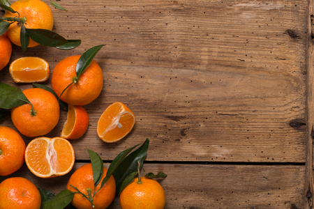 Group of fresh tangerines with leaves on wooden table. Top view and copyspace Imagens