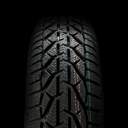 Close up of car tire  with water droplets isolated on black background. Front view Reklamní fotografie
