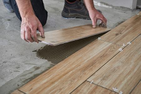 Hände des Fliesenlegers legen die Keramikfliesen in Holzoptik auf den Boden