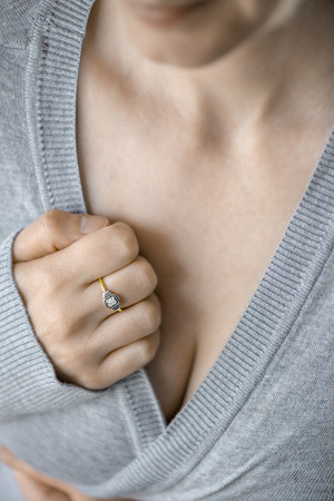 Close up of gold ring with stone on woman finger with grey sweater. Soft and selective focus
