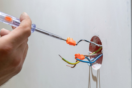 Closeup of electrician checking electrical current in a wire.
