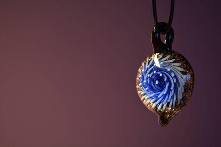 Glass pendant against a purple backdrop, horizontal Stock Photo