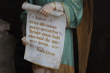 Figure of an angel holding a scroll with one of Jesus parables