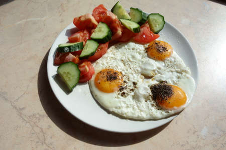 Three fried eggs with raw sliced ??cucumber and tomato