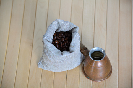 Canvas pouch of coffee beans and a Turkish brewing pot