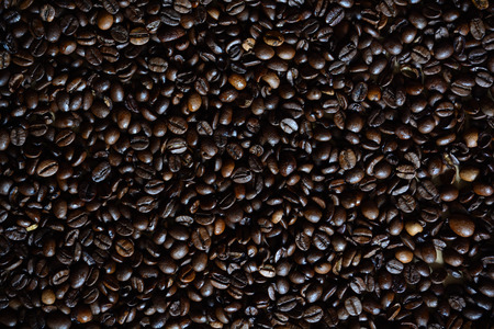Oily coffee beans spilled for a textured, delicious background Zdjęcie Seryjne