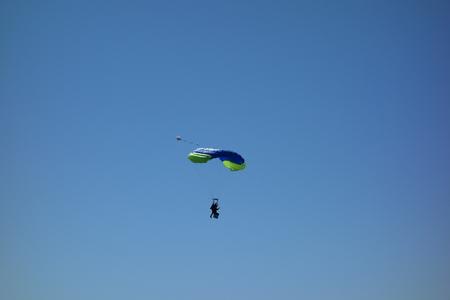 Tandem parachuting. Pair of parachutists in descent to landing Zdjęcie Seryjne
