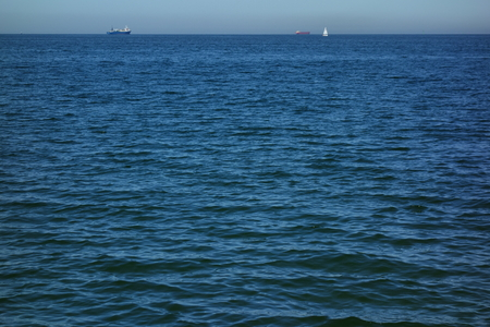 Seascape with cargo ships and a sailing boat