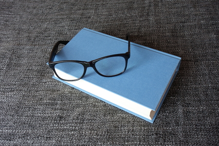 Blue hardcover and a pair of reading glasses