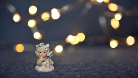 Little cherub against blurred Christmas lights