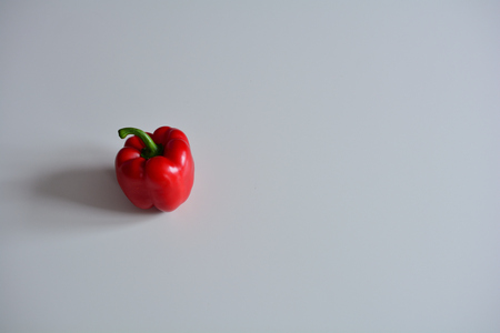 Red bell pepper on a smooth white surface