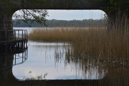 Lakeside landscape through a railway bridge span
