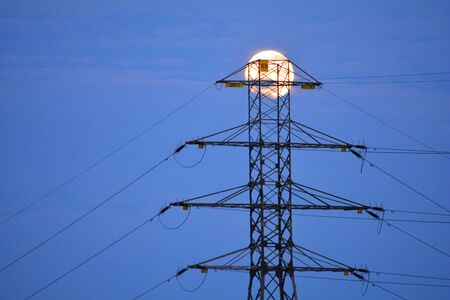 Power line pylon with a full moon in the background