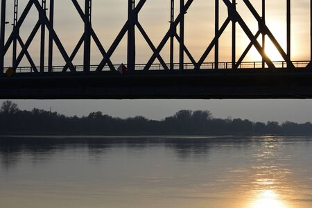 Truss bridge span against sunset reflecting on the water