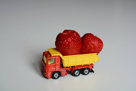 Fresh food delivery. Red yellow toy skipper loaded with strawberries Stock Photo