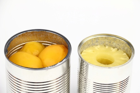 tinned: The tins with peaches and pineapples on the white background Stock Photo