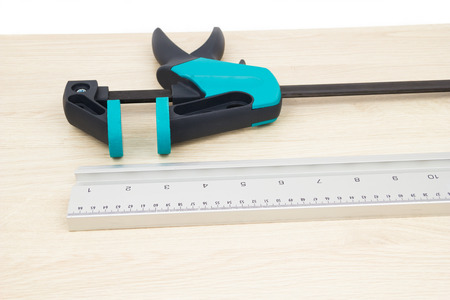 chipboard: Clamp carpentry and measuring strip on the chipboard Stock Photo