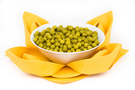 potherb: Folded napkin with green peas on the white background