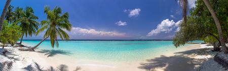 Beach panorama op de Malediven met blauwe hemel, palmbomen en turquoise water
