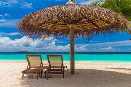 loungers: Dreamy beach with sun loungers under a beach umbrella at Maldives