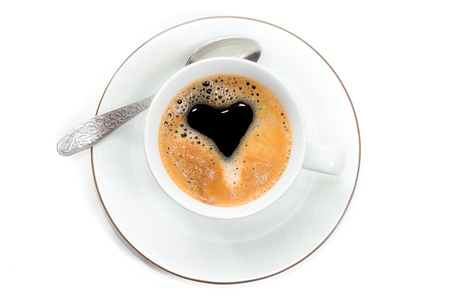Top view to cup of fresh brewed coffee with creama in form of heart