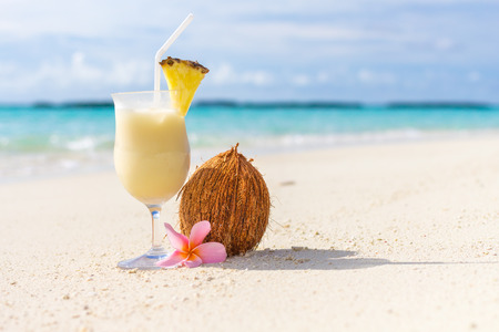 longdrink: Pina Colada cocktail on the beach with coconut and exotic flower