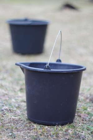 black bucket on grass in the garden photo