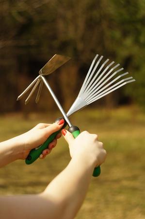 mani incrociate: Strumenti di giardinaggio in mani femminili incrociate