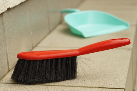 Brush and dustpan outdoors outside a house photo