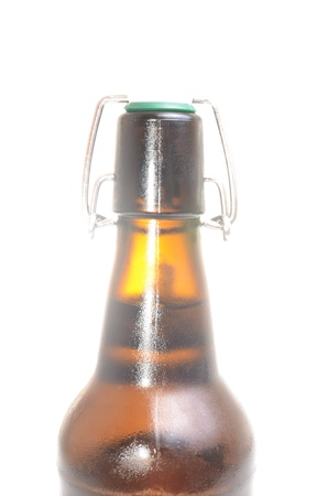 dewed: old brown bottle of beer isolated on white
