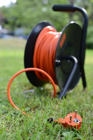 Orange electric cable in the garden photo