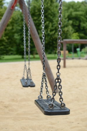 lonliness: Swings on playground in a park Stock Photo