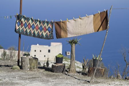 erice: Traditional handwoven carpets Frazate with geometric patterns, typically from Trapani province, getting dry outdoors in Erice. Stock Photo