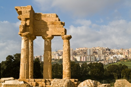 occupying: Ruins of Temple of Castor and Pollux in Valley of the Temples in Agrigento (Akragas), Sicily. New Agrigento in the background.